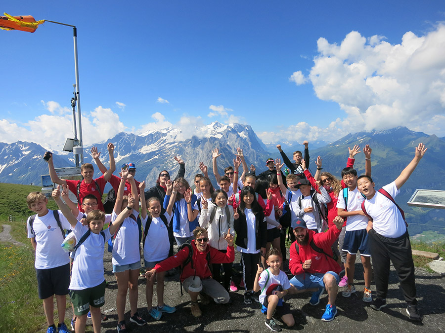 kids smiling in front of Swiss mountains